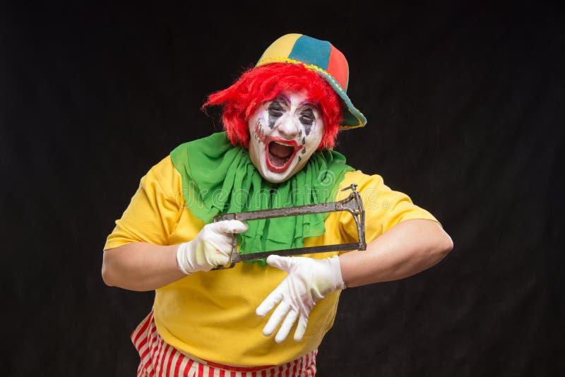 Pagliaccio spaventoso diabolico con capelli rossi su un fondo nero fotografia stock