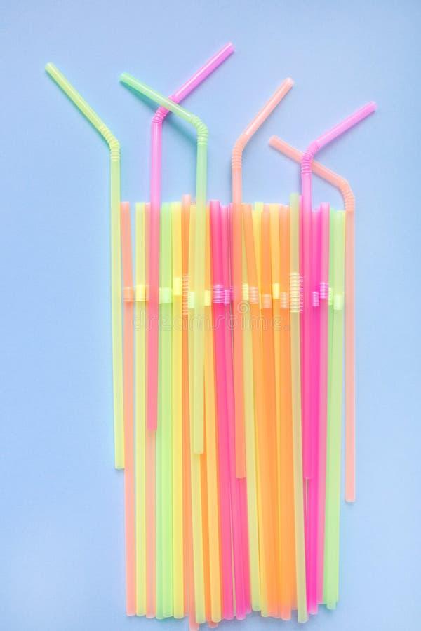 Paglie di plastica Colourful su fondo blu Tubi del cocktail immagini stock libere da diritti