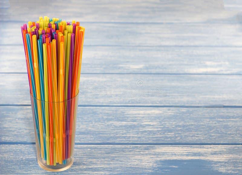 Paglie multicolori per bere in un vetro, fondo di legno blu, variopinto immagine stock