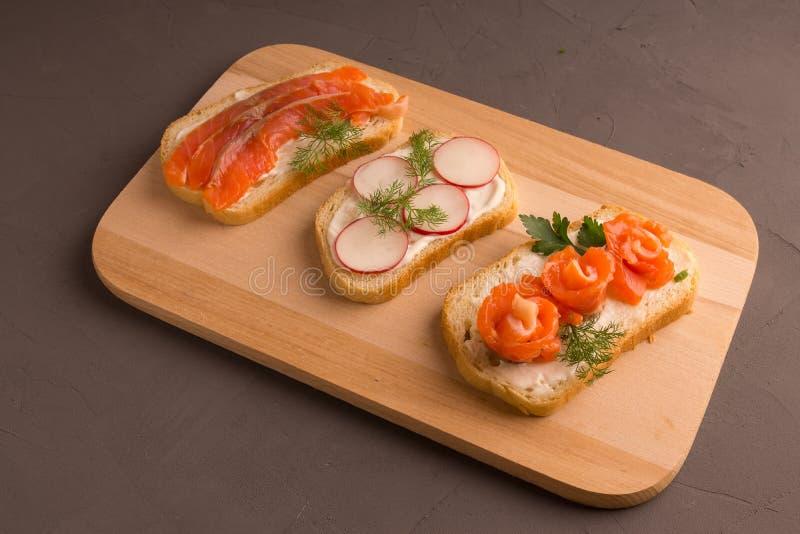 Pagnotta affettata con le fette di color salmone, pomodori ciliegia immagini stock