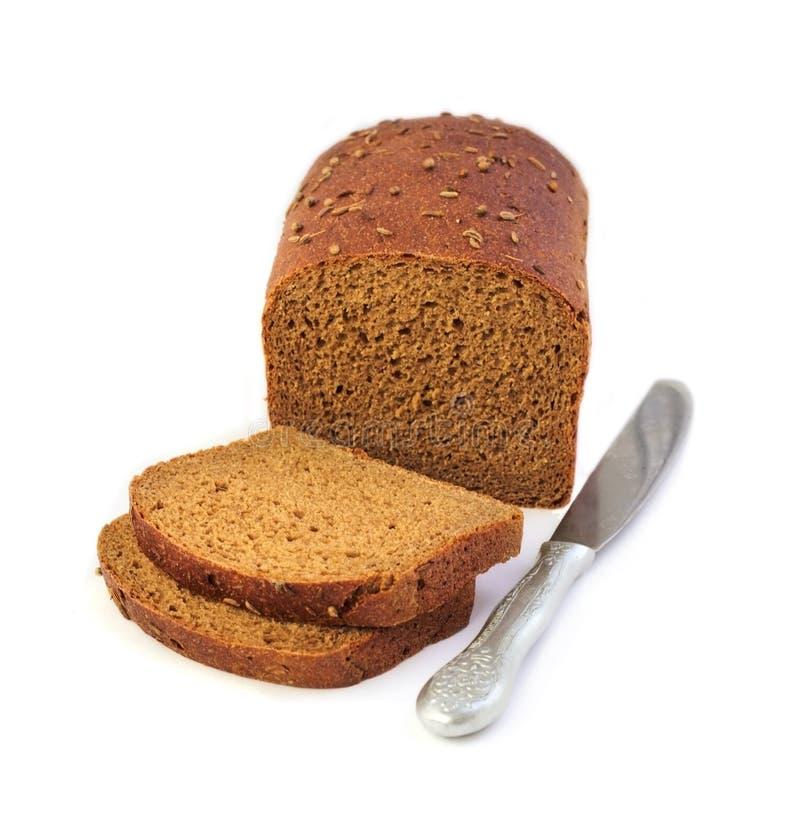 Pagnotta del pane di segale con le fette ed il coltello immagini stock
