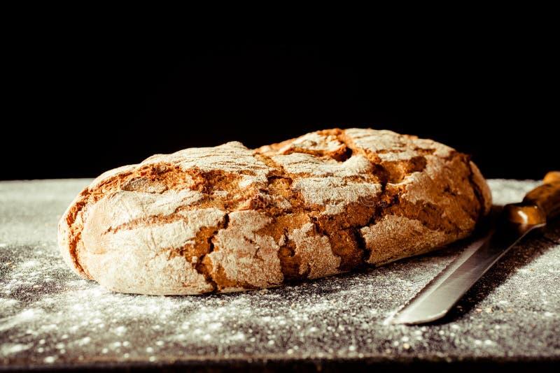Pagnotta del pane integrale incrinato di Artisinal con il coltello immagini stock