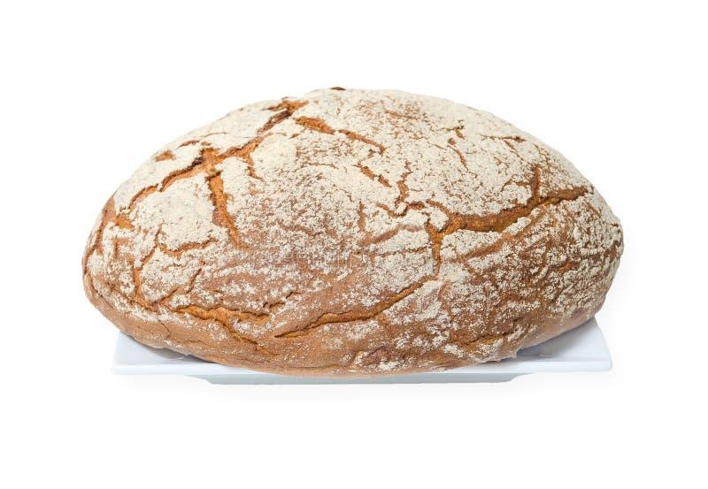 Pagnotta di Brown con farina spruzzata sulla cima su un piatto quadrato bianco su fondo bianco fotografia stock