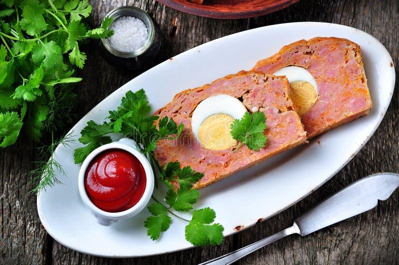 Pagnotta di carne con l'uovo sodo, la salsa al pomodoro, il coriandolo ed il prezzemolo su una tavola di legno Stile rustico immagini stock