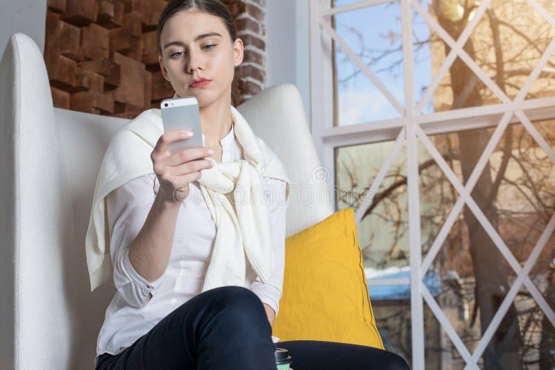 Pago confiado femenino del financiero en línea vía el teléfono de célula fotos de archivo