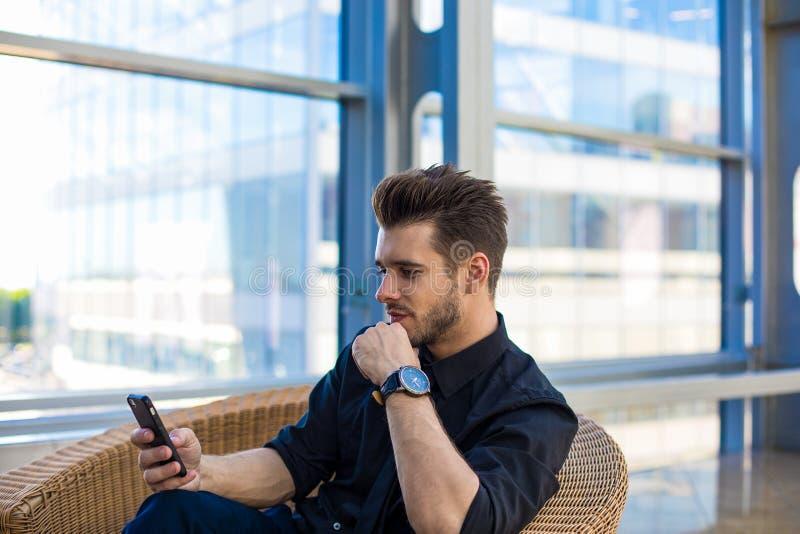 Pago en línea del banquero experto vía el teléfono móvil durante día del trabajo en compañía fotos de archivo libres de regalías