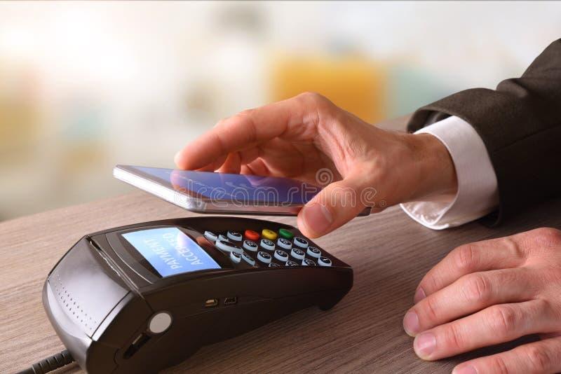 Pago en un comercio con tecnología móvil de NFC fotos de archivo libres de regalías