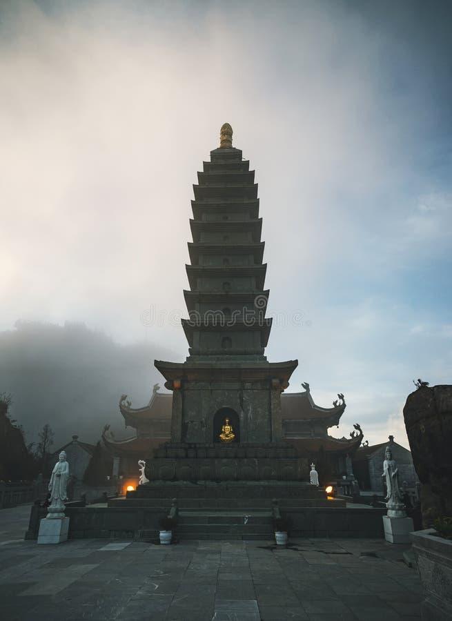 Pagoda de piedra en templo en la niebla contra el cielo azul con las nubes oscuras en la montaña más alta del pico de montaña de  imágenes de archivo libres de regalías