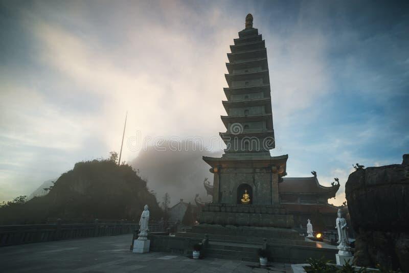 Pagoda de piedra en templo en la niebla contra el cielo azul con las nubes oscuras en la monta?a m?s alta del pico de monta?a de  imagen de archivo libre de regalías