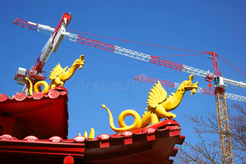 Pagoda, Dragons and Cranes. Part of a pagoda with dragons, machine cranes and a blue sky in the background royalty free stock photos
