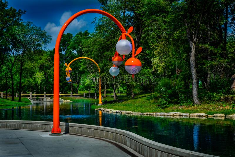 Pond feature in public park and lamp posts. stock photos