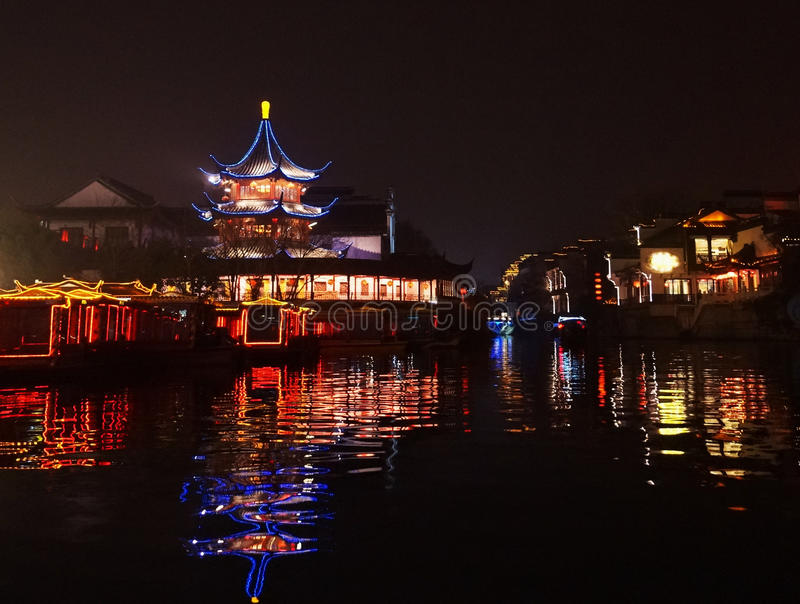 Pagoda outlined in light by the water. Pagoda and other buildings lit up at night at Fuzi Miao waterway hub, Nanjing, China. Reflections of colored lights in the stock images
