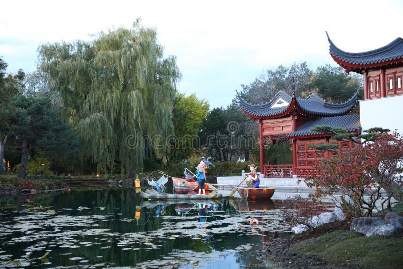 Pagoda sur le lac avec des lis et la réflexion du ciel et arbres dans l'eau photos stock