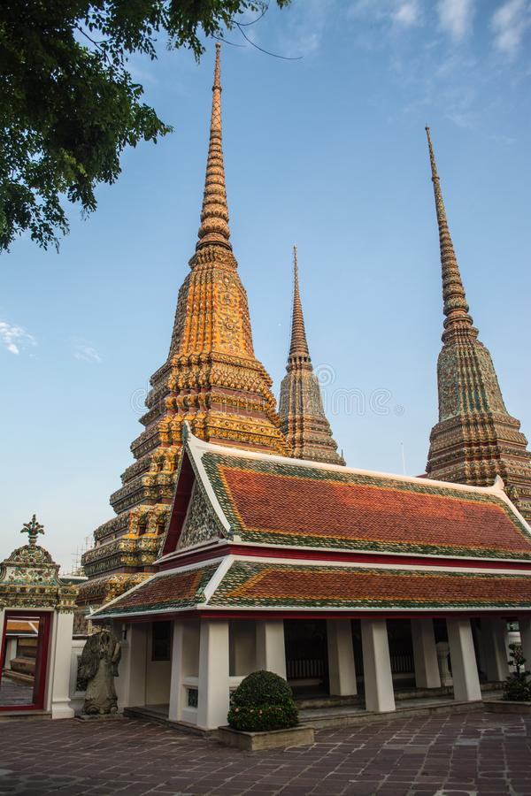 Pagoda is in Wat Pho that was named as the temple of the pagoda. Or chedi that are decorated with yellow glaze or glazed tiles or dark blue stock image
