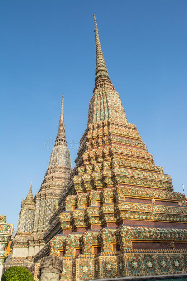 Pagoda is in Wat Pho that was named as the temple of the pagoda. Or chedi that are decorated with yellow glaze or glazed tiles or dark blue stock images