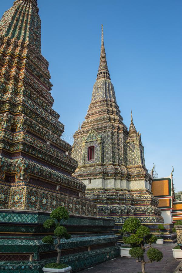 Pagoda is in Wat Pho that was named as the temple of the pagoda. Or chedi that are decorated with yellow glaze or glazed tiles or dark blue stock photography