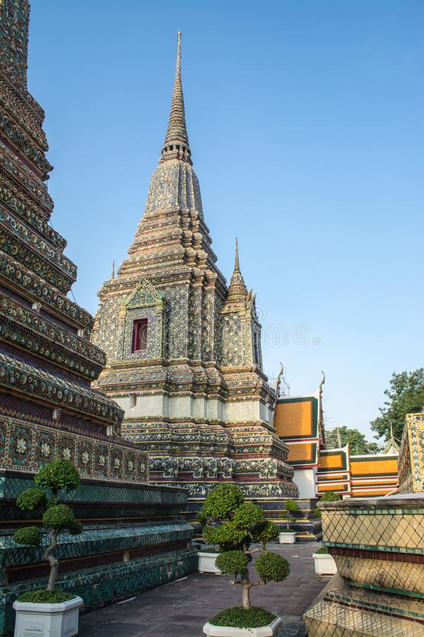 Pagoda is in Wat Pho that was named as the temple of the pagoda. Or chedi that are decorated with yellow glaze or glazed tiles or dark blue stock photo