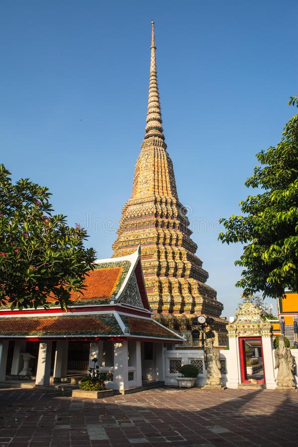 Pagoda is in Wat Pho that was named as the temple of the pagoda. Or chedi that are decorated with yellow glaze or glazed tiles or dark blue royalty free stock photo