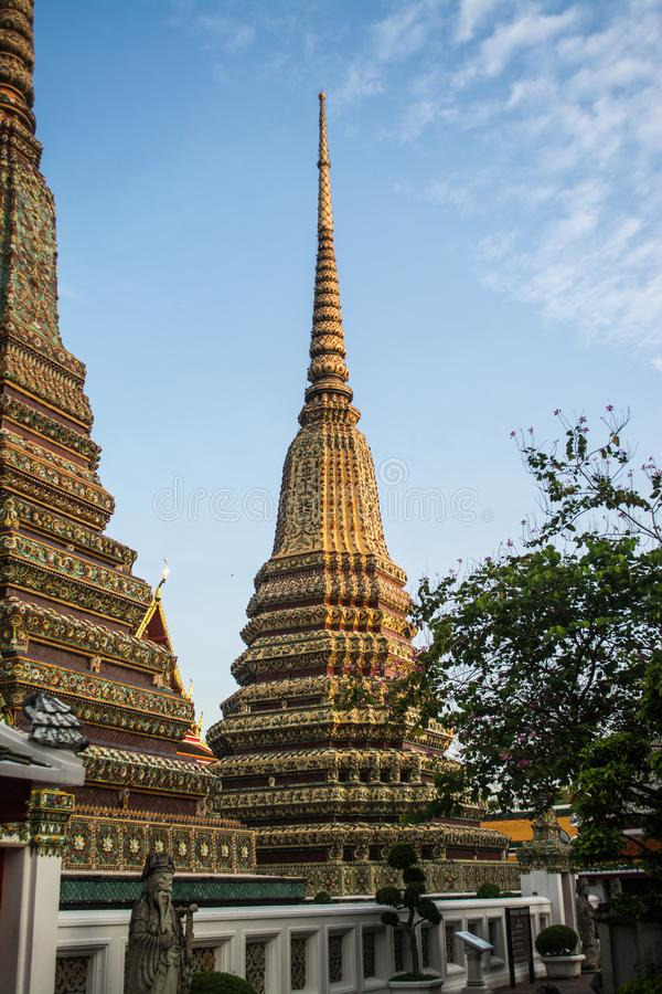 Pagoda is in Wat Pho that was named as the temple of the pagoda. Or chedi that are decorated with yellow glaze or glazed tiles or dark blue stock photos