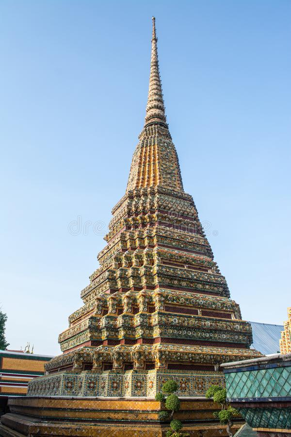 Pagoda is in Wat Pho that was named as the temple of the pagoda. Or chedi that are decorated with yellow glaze or glazed tiles or dark blue royalty free stock images