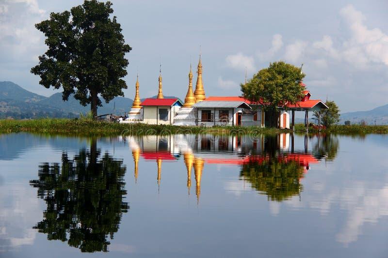 Pagode mit roten Dachspitzen und goldenen Helmen in der Spiegelung im See Inle, Myanmar/Birma stockbilder