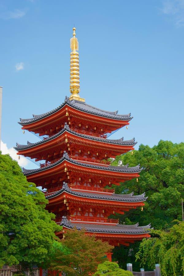 Pagode vermelho vívido em Fukuoka, Japão Pináculo dourado de incandescência e árvores verdes fotos de stock
