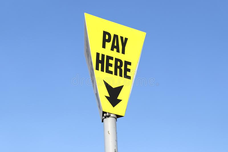 Pague aqui o sinal pelo estacionamento do carro contra o céu azul fotos de stock