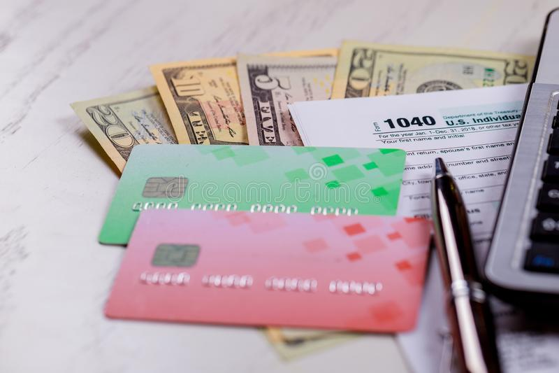 Pague o formulário de imposto 1040 dos EUA do conceito do imposto com notas de dólar dos E.U. e para April Calendar imagens de stock royalty free