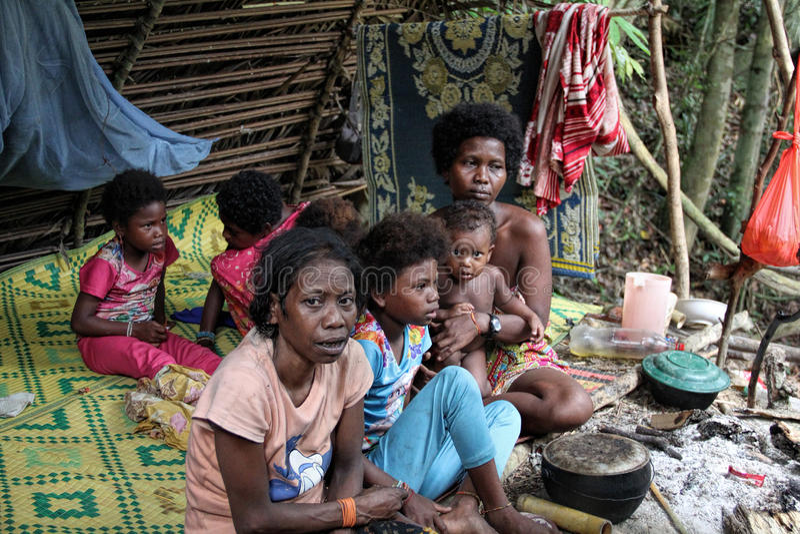 PAHANG, МАЛАЙЗИЯ 9-ОЕ ДЕКАБРЯ 2015: женщины и дети индигенного племени Batek Negritos малайзийца отдыхая в их стоковые изображения