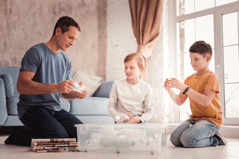 Pai adotivo diligente que diz seus filhos sobre a reciclagem do lixo imagens de stock royalty free