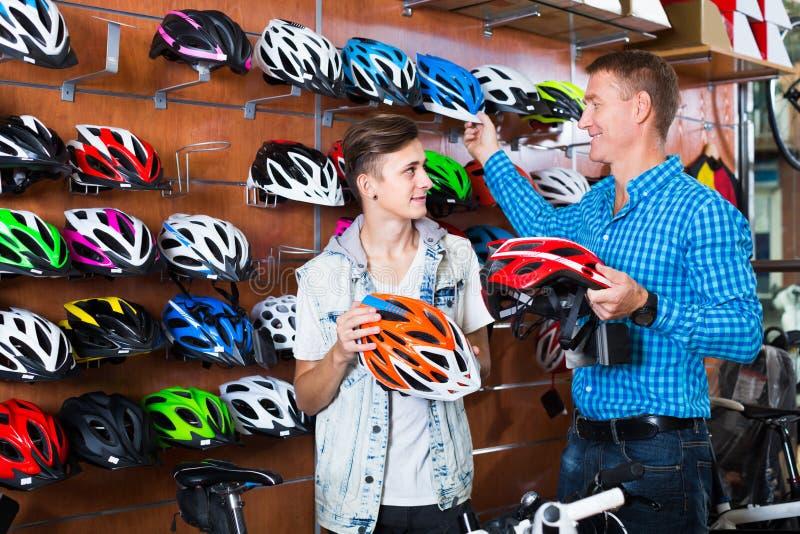 Pai adulto e filho que escolhem o capacete bicycling imagem de stock
