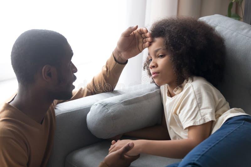 Pai africano de inquietação que toca na testa da filha doente da criança fotos de stock