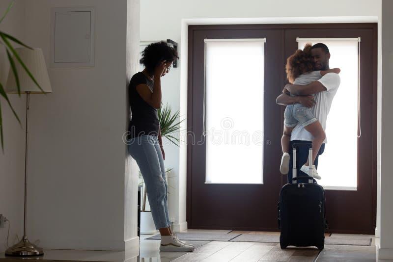 Pai africano triste que abraça pouca filha antes de deixar a família imagens de stock royalty free