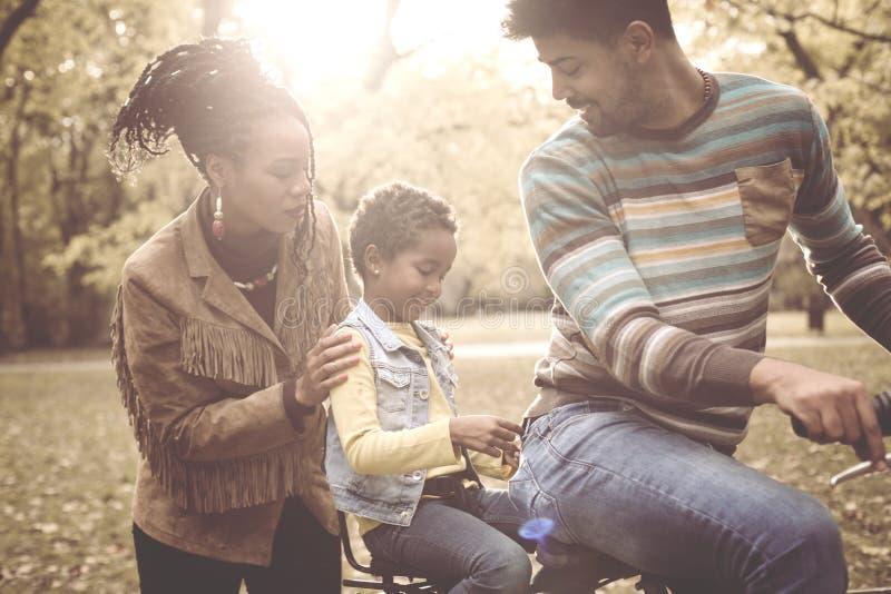 Pai afro-americano alegre que conduz a filha na bicicleta foto de stock royalty free