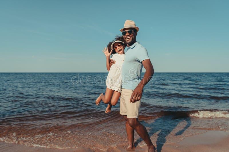 pai afro-americano de sorriso e filha pequena bonito nos óculos de sol que têm o divertimento junto imagens de stock royalty free