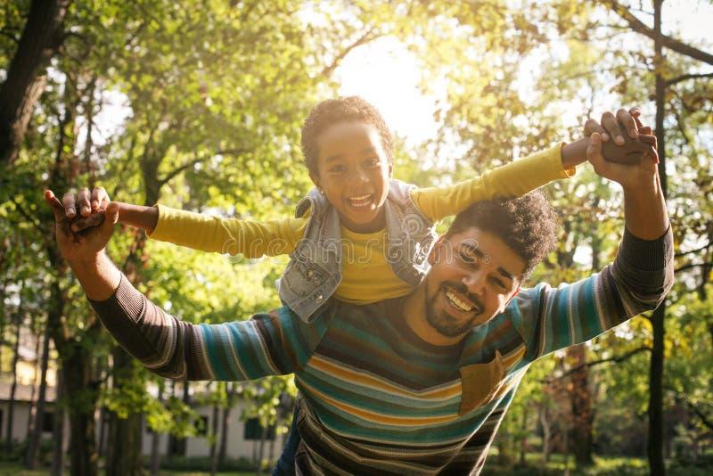 Pai afro-americano de sorriso que leva sua filha no piggyba imagem de stock