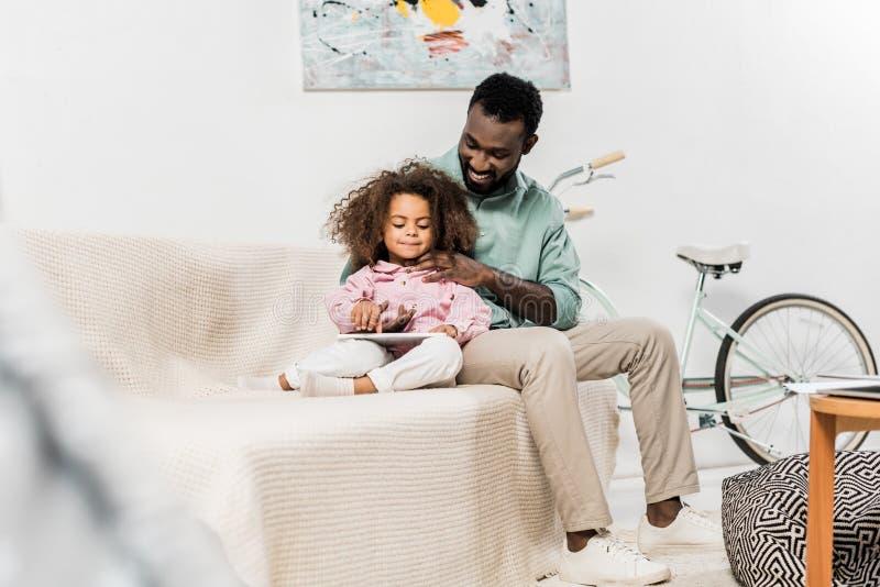 pai afro-americano e filha que sentam-se confortavelmente no sofá e fotos de stock royalty free