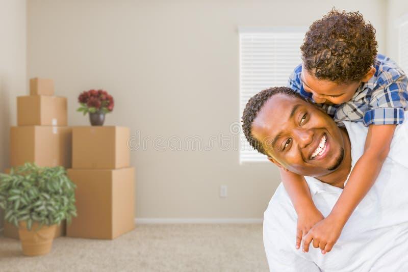 Pai afro-americano e filho da raça misturada na sala com M embalado imagens de stock