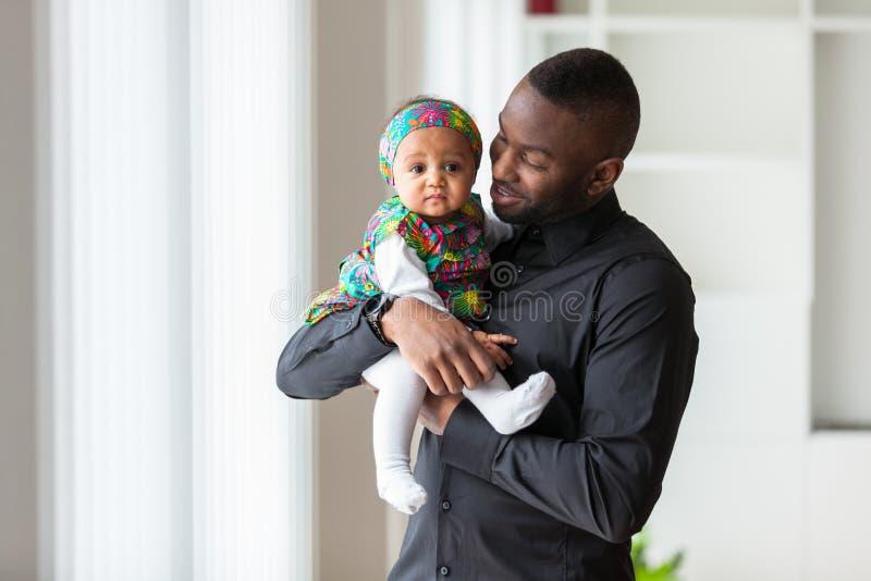 Pai afro-americano novo que guarda com seu bebê imagens de stock royalty free