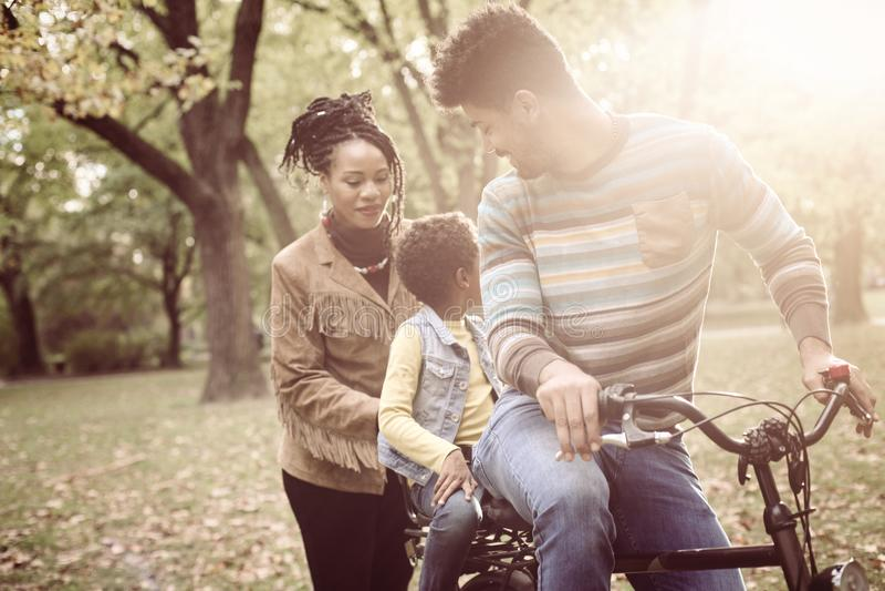 Pai afro-americano que conduz a filha na bicicleta fotografia de stock royalty free