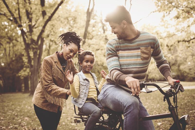 Pai afro-americano que conduz a filha na bicicleta imagens de stock royalty free