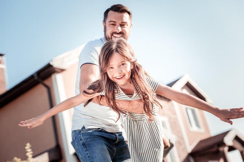 Pai agradável de inquietação que sorri e que apoia sua filha fotos de stock
