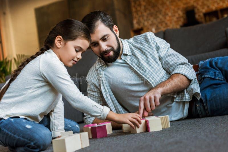 pai alegre com a filha que faz palavras por cubos com letras imagem de stock