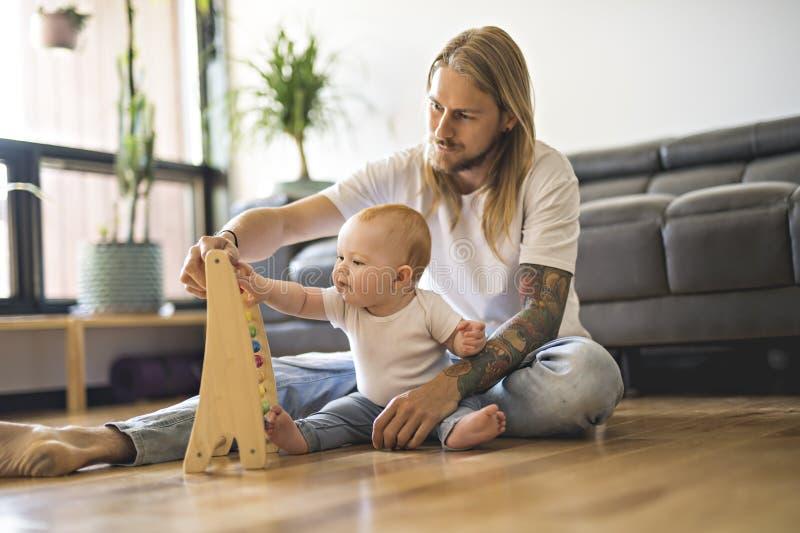 Pai alegre que joga com seu bebê no assoalho na sala de visitas imagem de stock