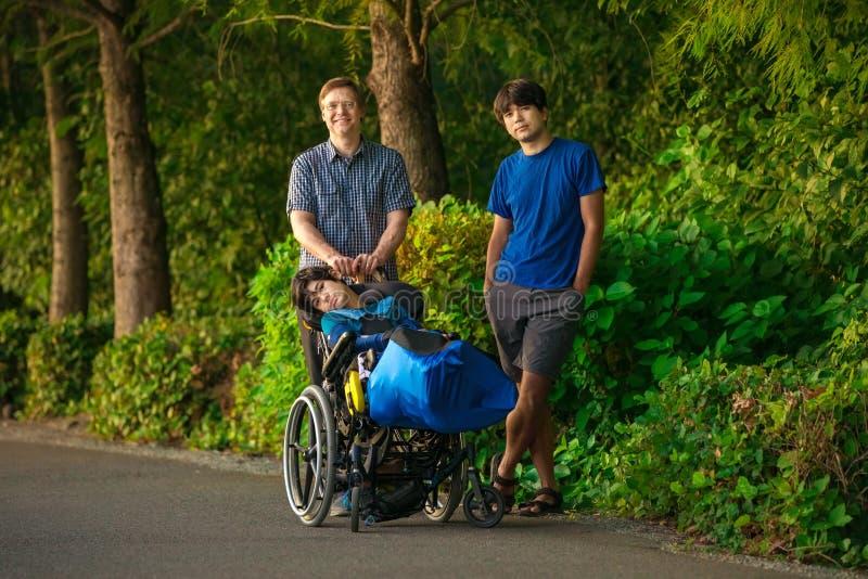 Pai andando com dois filhos, uma criança com necessidades especiais em cadeira de rodas imagens de stock