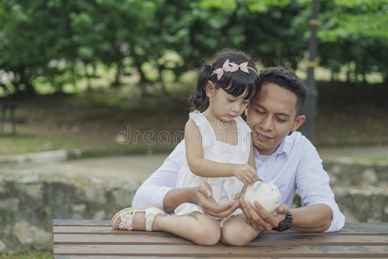 Pai asiático novo para ensinar sua filha ao dinheiro de salvamento no mealheiro para o melhor futuro fotografia de stock