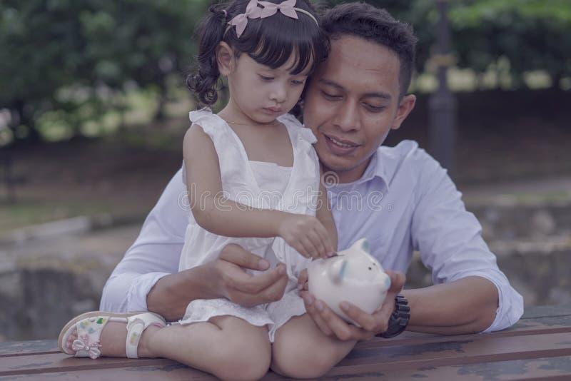Pai asiático novo para ensinar sua filha ao dinheiro de salvamento no mealheiro para o melhor futuro imagem de stock