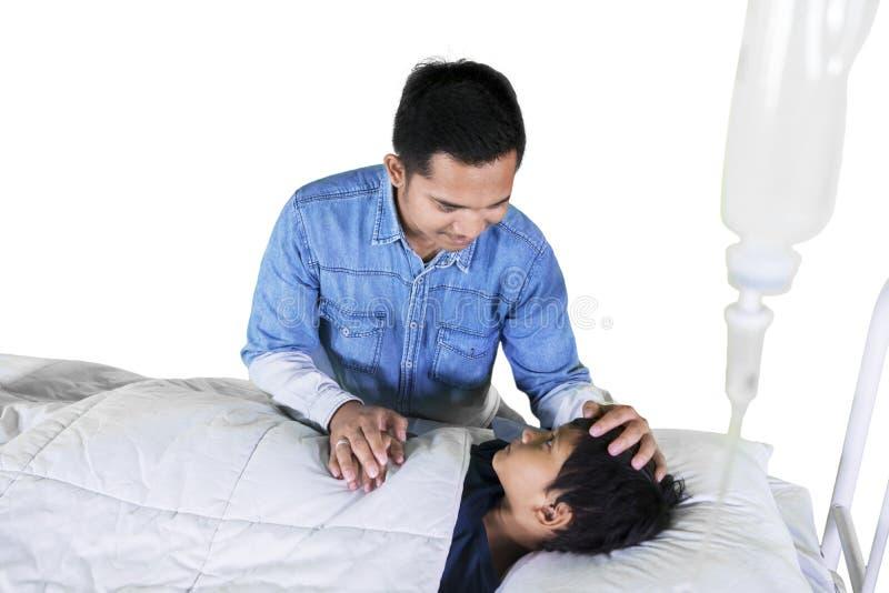 Pai asiático que toma de seu filho doente no estúdio imagens de stock royalty free
