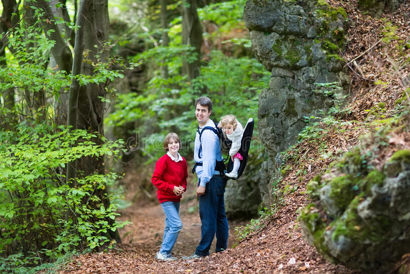 Pai ativo novo que caminha no penhasco e na floresta com crianças fotografia de stock royalty free