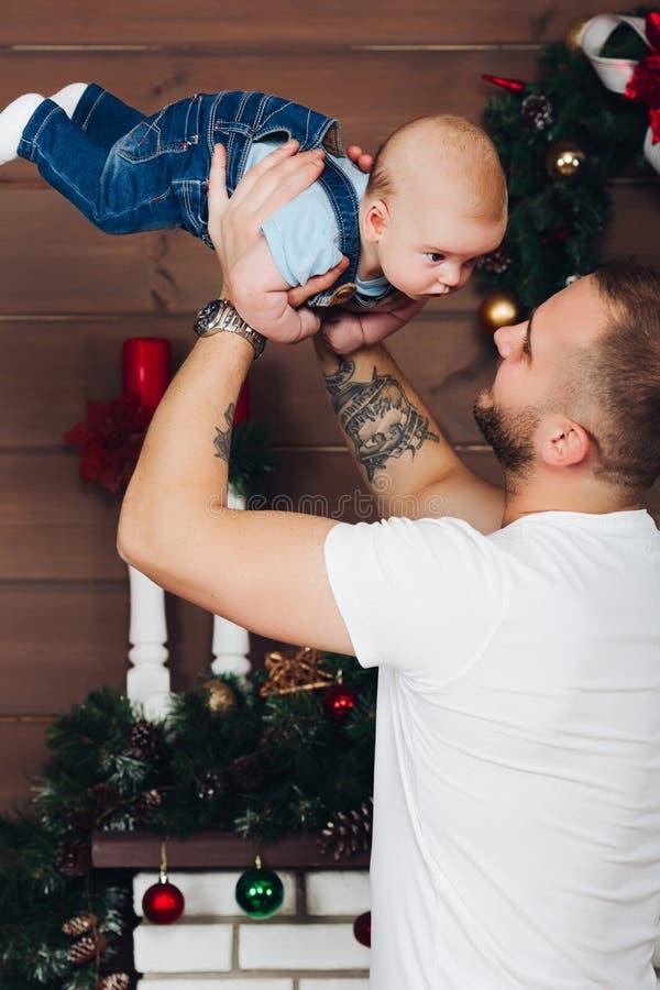 Pai bonito e feliz que mantém o filho pequeno pelas mãos, aumentando ele fotografia de stock